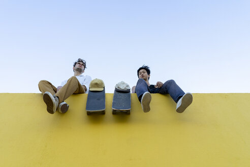 Two young men with skateboards sitting on a high yellow wall - AFVF01497