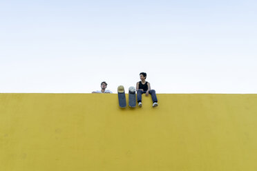 Two young men with skateboards at a high yellow wall - AFVF01500