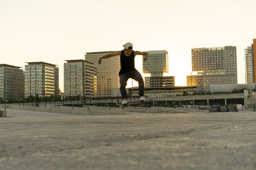 Young man doing a skateboard trick in the city at sunset - AFVF01503