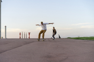 Two young men riding down a lane with skateboards - AFVF01506