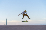 Young man doing a skateboard trick on a lane at dusk - AFVF01512