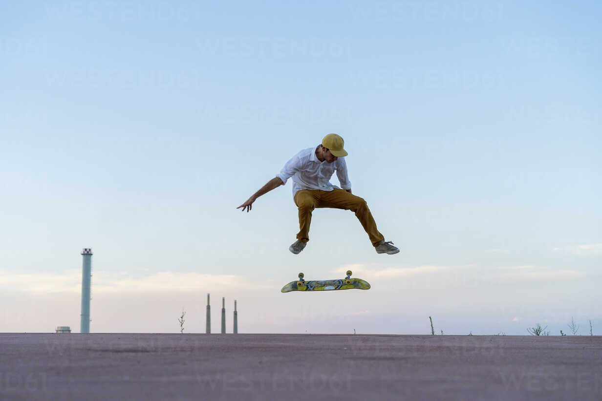 Young man doing a skateboard trick on a lane at dusk - AFVF01512 - VITTA GALLERY/Westend61