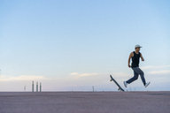 Young man running next to skateboard on a lane at dusk - AFVF01515