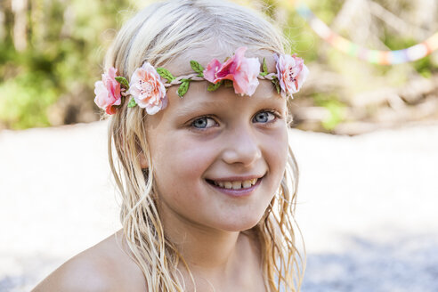 Portrait of smiling girl wearing flower crown outdoors in summer - TCF05755