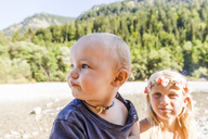 Portrait of baby boy and girl wearing flower crown outdoors in summer - TCF05758