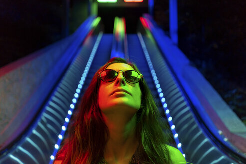Portrait of illuminated young woman wearing sunglasses in front of blue lighted escalator - AFVF01526