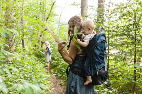 Woman hiking in the woods showing large leaf to baby boy in backpack - TCF05766