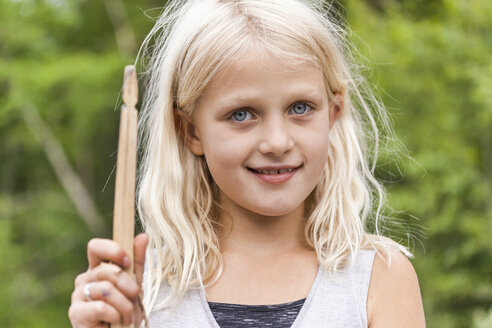 Portrait of smiling girl holding wooden stick outdoors - TCF05772
