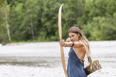Archeress aiming with a bow in the nature - TCF05781