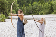 Mother and daughter aiming with bow and arrow in the nature - TCF05787