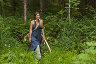 Smiling woman walking in a forest with bow and arrow - TCF05790