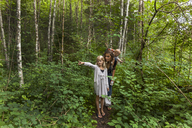 Girl hiking in the woods showing the way to mother and little brother - TCF05799