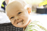 Portrait of smiling baby boy with smeared face outdoors - TCF05802