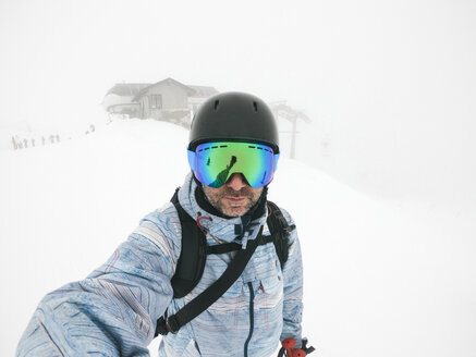 Italy, Modena, Cimone, portrait of man wearing ski goggles and helmet in haze - JPIF00002