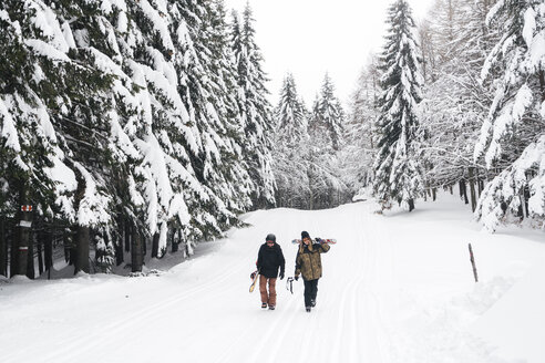 Italy, Modena, Cimone, couple with skiers and snowboard walking in winter forest - JPIF00008