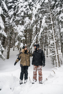 Italy, Modena, Cimone, skiing couple standing in winter forest - JPIF00014