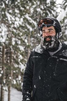 Smiling young man in skiwear in winter forest looking sideways - JPIF00017