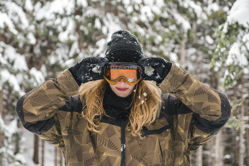 Young woman putting on ski goggles in winter forest - JPIF00020