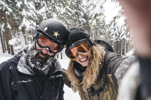 Selfie of smiling couple in skiwear in winter forest - JPIF00023