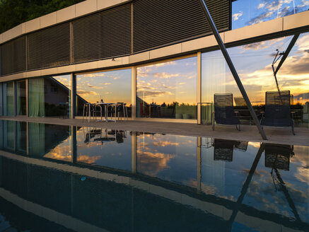 Switzerland, glass front of modern villa at dusk with terrace and pool in the foreground - LAF02075