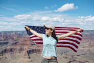 USA, Arizona, smiling woman with American flag at Grand Canyon National Park - GEMF02357