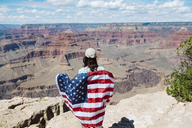 USA, Arizona, smiling woman with American flag at Grand Canyon National Park, rear view - GEMF02366