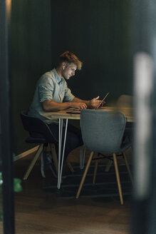 Man sitting in office, working late in his start-up company - GUSF01223