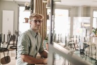 Young business owner sitting in his coffee shop, using laptop - GUSF01262