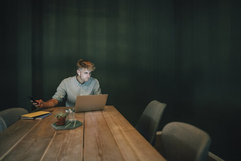 Man sitting in office, working late in his start-up company, listening music - GUSF01268
