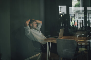 Man sitting in office, working late in his start-up company - GUSF01274