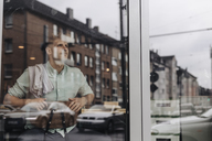 Young business owner sitting in his coffee shop, daydreaming - GUSF01283