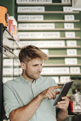 Young business owner using digital tablet in his coffee shop - GUSF01289