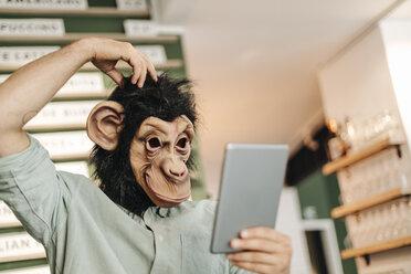 Man wearing monkey mask, using digital tablet, scratching head - GUSF01292