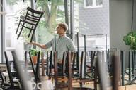 Man balancing chair on his hand, closing his coffee shop - GUSF01298