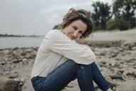 Woman relaxing at the river, looking at camera - KNSF04347