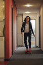 Mature businesswoman rollerskating in office corridor - KNSF04368