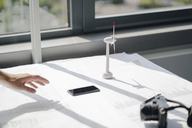 Hand of man reaching for smartphon lying on desk with blueprints and wind wheel - KNSF04377