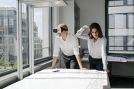 Two architects working on blueprints, man using VR glasses - KNSF04383
