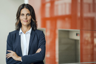 Portrait of a successful businesswoman, standing in front of elevator, with arms crossed - KNSF04389