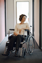 Disabled business woman sitting in wheelchair, with laptop on knees - KNSF04395