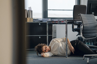 Tired businesswoman sleeping on floor under her desk - KNSF04401