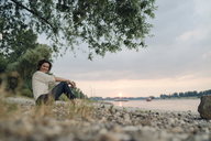 Woman sitting at the river, watching sunset - KNSF04404