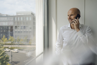 Smiling businessman standing in his office, talking on his mobile phone - KNSF04428