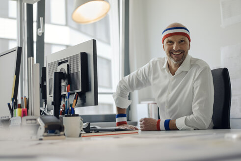 Businessman sitting in office, wearing sweat bands - KNSF04431