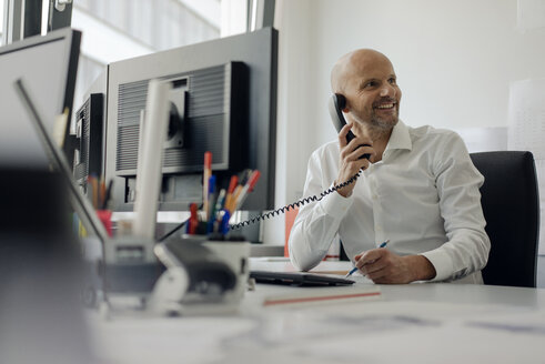 Smiling businessman sitting at his desk, talking on the phone - KNSF04437