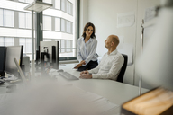 Businessman and woman working together in office - KNSF04440