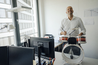 Businessman making noise with drums in his office - KNSF04449