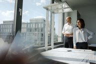 Two architects standing in office, looking out of window - KNSF04455