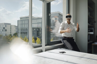 Businessman standing in his office, using VR glasses - KNSF04458