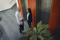 Business people talking in front of elevator - KNSF04464